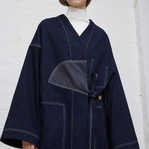 Rigtig størrelse er 34.  Den er meget Oversize - kan passes fra S-L  Sælger denne smukke frakke fra Acne Studios i mørkeblå denim med tydelige syninger, to store lommer foran, V udskæring og bindebånd. Den er brugt 3 gange og fremstår helt som ny.   Ny pris 6.500 kr.