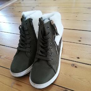 Nye armygrønne ankelstøvler. De har indvendig kilehæl på ca. 6 cm og blødt stof rundt om anklen uden på skoen (i hvidt) samt blødt stof indvendigt. De har også en fin guld lynlås-detalje på ydersiden. De er str 38. Aldrig brugt. Byd gerne 😊 (jeg sender også gerne flere billeder)