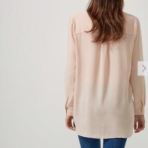 Varetype: Bluse Farve: Pudder - Loose fit - 100% Polyester - Lange ærmer - Knappestolpe - Længere på ryg - Let kvalitet, ikke gennemsigtig.  Sælger også i andre farver, samme model.