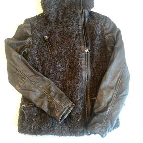 """Lækker jakke i uldbouclé og skind ( ærmer i skind) den er ikke brugt meget ( 10-12 gange) men nogle at de påsatte """"nitter"""" på skuldrene er faldet af."""