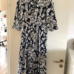 Elegant lang kjole i blomstermønster fra Soyaconcept. Kjolen har knapper hele vejen ned.  Brugt max. 5 gange.  Nypris kr. 500,- Sælges for kr. 100,- plus porto eller afhentet i Odense S Bytter ikke.