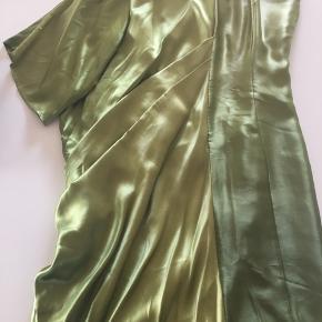 Smuk og meget speciel grøn kjole af silke. Den ene side er glat og kropsnær, og den anden side er draperet og med ærme. Aldrig brugt!