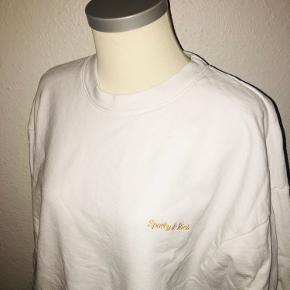 Hvid sweatshirt fra sporty & Rich i størrelse large. Med lille broderet guld logo på fronten.