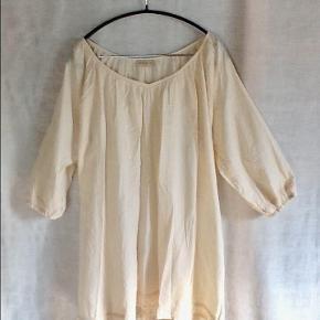 Smuk og feminin tunika / kort kjole / top fra MASALA. 100 % bomuld. Flot halsudskæring og blonder langs ærmeafslutning og langs underkanten. Længde fra skulder til underkant : 85 cm. Brystmål : 2 x 70 cm. Mange læg -> masse af plads, men falder flot. Aldrig brugt - vasket en enkelt gang for at friske den op efter ophold i skabet. Tunika / kort kjole Farve: Råhvid Oprindelig købspris: 400 kr.  Sender gerne på købers regning : DAO 39,-