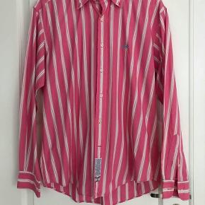 Varetype: herre skjorte Farve: Pink Oprindelig købspris: 2000 kr.   Herre La Martina . Flot pink skjorte. str. Xl. Meget fin stand. Nypris 2000kr. Porto 38kr.