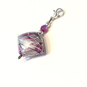 Charm fra Walina  Vedhæng til tasker punge halskæder  Lilla og grå charm, med matchende perler.  Brug den som pynt til: - din lynlås til dit penalhus, taske eller pung - din nøglering - din eksisterende halskæde  I alt er den 4 cm lang.  Jeg kan handle med mobilpay: Jeg sender gerne med post nord til din postkasse (+10 kr 5 dages leveringstid eller 29 kr 1 dags leveringstid), hvis du ikke kigger forbi og henter den. Jeg kan handle via Tradono med DAO pakkepost (+32 kr), hvor du afhenter pakken ved ønsket DAO udleveringssted  Mvh Lise