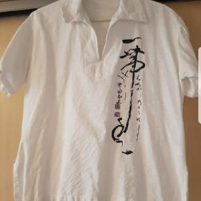Bluse med v udskæring ved hals og med halskrave. tryk på hele venstre side.  I fin stand  Str. L. Fra Thailand. Mp 20 kr.  Sender ikke...