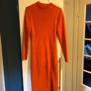 Aldrig brugt! Flot orange overgangskjole i bomuld med lille slids. Den er lang, går mig til midt på skinnebenet (jeg er 175cm høj cirka) figur syet. Tætsiddende. Meget bred/varierende i størrelse (størrelse S-L) der er masser at stræk i