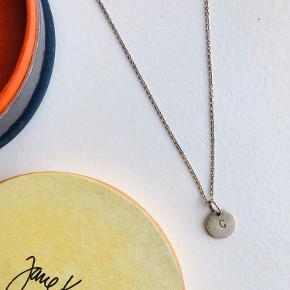 """Fin halskæden med 'C' vedhæng fra Jane Kønig. Fejler intet men kunne godt trænge til en omgang puds, da det har """"ligget stille længe"""". Lås er klemt sammen, som det ses på billedet."""