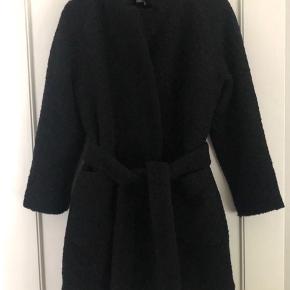 Ganni's klassiske jakke, brugt i ca 14 dage.  Frakke til over knæet lavet i en uldblanding med tekstur og aftageligt bælte, knaplukning ved taljen samt dybe, påsatte lommer.  Bytter ikke.