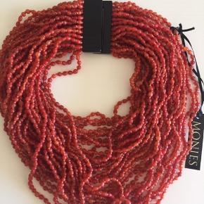 Ny og ubrugt halskæde fra Monies. Farven er orange-rød. Korteste indvendig mål: ca. 39 cm + lås: 3 cm i alt  42 cm på det korteste sted. Låsen er sort og højden er: 5,5 cm Halskæden er ikke tung: Den består af fine små sten i orange (materiale ukendt) og smuk orange (silke?) tråd mellem alle sten. MP kr. 995,00 pp Bytter ikke.