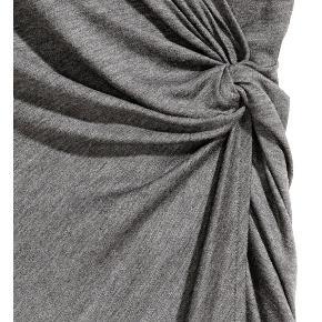 Anden kjole, H&M, str. M, Grå, Ubrugt  Feminin lang (midi) ærmeløs kjole i blød 100% viscosekvalitet. Den er krydset foran med en dekorativ knude. Den har taljesøm og drapering og er foret. Den er helt ny og ubrugt. Nypris: 249 kroner. Eventuel fragt lægges oveni: 38 til nærmeste posthus/butik.