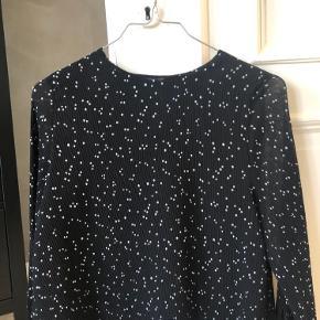 Fin bluse med små hvide prikker. Den har åbne ærmer, hvor den bliver samlet med en sløjfe. Obs blusen er længere end en Croo top, men kortere end en alm bluse. Skriv endelig for yderligere spørgsmål eller billeder.