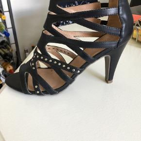 sort sandal, str 38, kun brugt få gange, tror det er skind, men ikke helt sikker. hæl højde er 9 cm.