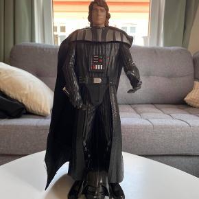 Hej! Jeg sælger denne Darth Vader / Anakin Skywalker figur. Figuren er med en aftagelig maske. Figuren laver hans vejrtrækning lyd hvergang du tager masken på ham, og har en knap på sig, hvor den siger en lyd som et lyssværd. Desværre mangler figuren sit lyssværd. Den er 33 cm høj. Jeg sælger den til 125 kr. Hvis du har nogle spørgsmål til den, så spørg løs!