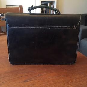 Super flot retro - vintage taske i mørkebrun kernelæder. Flot haspe og med fin ornamentik udenpå. Tre store rum og et lille. Der er ingen lang rem, men der er hægter så, der kan sættes en lang rem på. Standen er rigtig god med få brugsspor. Mål: 34*25*9 cm