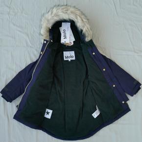 """Varetype: *NY* vinterjakke Størrelse: 116 Oprindelig købspris: 1.499 kr.  Super flot vinterjakke fra Molo, som aldrig har været brugt - mærket sidder stadig i.  Den er vindtæt, 100% vandtæt (vandsøjletryk 10.000) og åndbar. Er foret med fleece og har aftagelig hætte med aftagelig kant af kunstpels.  Style: """"Peace"""". Farve: """"Evening Blue"""".  Modellen er smal, så jeg tror, den vil passe bedst til en slank pige. Her er et par mål:  - Bredde (fra armhule til armhule): ca. 35 cm. - Længde (fra nakke og ned): ca. 64 cm (foran er den lidt kortere). - Indvendig armlængde (fra armhule og ned til håndled): ca. 32 cm.  Bud fra 750 kr. pp.  Jeg bytter ikke, men handler gerne via Mobilepay :-)"""