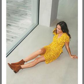 Smuk gul blomstret kjole fra mbym. Faconsyet med lynlås og bindedetalje i siden.  Ny, stadigvæk med prismærke.  Np 600