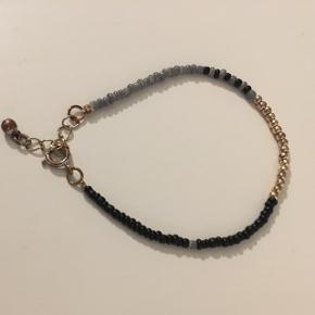 Rigtig fint perle armbånd fra Matas. Det består af guld, sorte og grå perler