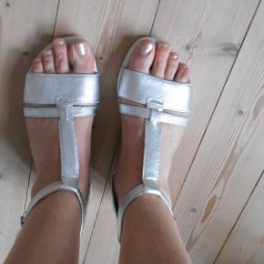 Beskrivelse Flotte  Nye sandaler i sølv. Er mærket str 4,5, der passer en str 38. Med lille hæl på 3 cm Fodlængde målt indvendig fra 23,5 cm.  Kan reguleres ved ankel og kan trykkes på plads med tryklås, og der dermed nemme at komme i. Lette i vægt. Sendes med DAO. Inkl porto.Bytter ikke.