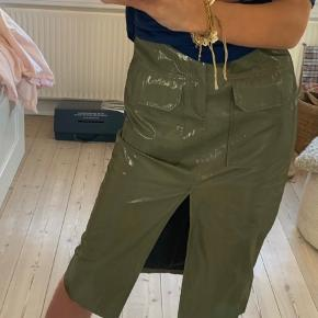 Sælger denne army grønne lak nederdel fra ZARA. Den er str. XS/S og der er elastisk foroven, hvormed den er justerbar. Den har aldrig været brugt - skriv for flere billeder eller mere information!