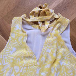 Smukkeste gule kjole uden ærmer. Lukkes med bindebånd i nakken. Dobbeltlag, så er ikke gennemsigtig. Længde 90 cm. Brystvidde 50*2 cm.