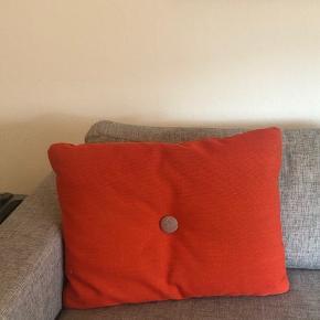 Sofapude i flot orange farve med knapper i mørkerød og grå.  Puden måler 60*45 cm.  Nypris ca 800kr.   Se også min annonce for den lyseblå Hay-pude. Sælger begge for en samlet pris på 500kr.