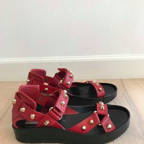 Super flotte og behagelige Balenciaga platform leather sandals. Str 39,5.  Ikke brugt meget, meget fin stand.  Købt i Dubai. Nypris 6000.-   Der er lavet en reparation indvendig øverst på skoens platform sål, af en professionel. Der er påsat et ekstra stykke sort skind, grundet en mindre revne i sålens øverste kant. Det sker som regel altid på platform sko, da sålen er tyk og ikke så smidig. Det har ingen øvrig betydning for skoens komfort og anvendelighed. ( kan ses på foto ) . Pris er sat herefter.  Porto er 50 kr.  Betaling over mobilpay.   Nederdelen er fra ETRO, se anden annonce.