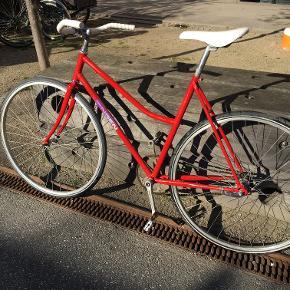 Fin rød Jensen dame-racer til de hurtige A-B ture i byen.  Cyklen er med et gear og fodbremse. Derudover har jeg skærm til bagdækket som kan hæftes af/på som man ønsker.  Kender ikke stelstørrelsen men jeg er selv 168 høj... og jeg passer den fint.   Let og ok velholdt (har stået ude denne vinter men ellers indedøre). Trænger da til en kærlig hånd og evt et nyt kranksæt.  Jeg har stelnummer og original kvittering. Købte den i tidernes morgen af en gut som bygger cykler udfra gamle dele, så måske den også er oplagt at bygge videre på eller bruge som reservedele.