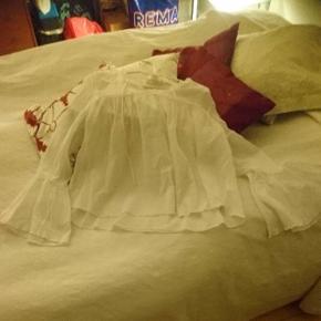 Hvid bluse med store ærmer forneden. Er letter gennemsigtig. Str 40. Måler 60 cm fra skulder til bund