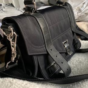 """Jeg sælger min super fine Proenza Shouler bag, stoffet er vandafvisende og tasken kan dermed tages med i den lette regn uden ydeligere skade.  Remmen er justerbar.   Jeg købte tasken hel som ny af en dame tilbage i marts, og den er derfor kun blevet brugt i få måneder, dermed i super god stand!💜   Der dog kommet et lille træk af læderet på indersiden af tasken som vist på billedet. Dette lægges der ikke yderligere mærke til.   Dustbag og kvittering haves ikke, dog haves kortet med """"Item number"""".   Skriv gerne for ydeligere spørgsmål 🥰"""