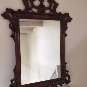 Smukt vægspejl i med mørk ramme i træ. Mål på ramme 106 cm x 71 cm. Selve spejlet måler 61 cm x 41 cm.  Der skal måske sættes et nyt beslag bagpå.