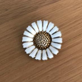 Klassisk elegant hvid Broche, velholdt, med forgyldninger fra Lund Copenhagen Brochen er i sterling sølv med en hvid emalje på bladende og elegant forgyldt imellem bladende og på knoppen Brochen måler 25 mm i diameter og kan også bruges med en kæde som vedhæng Nypris 750