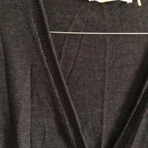 Fin tynd uld med perlemorsknapper. 88 cm lang.