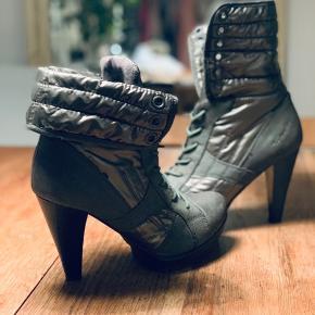 Mørkegrå fede støvler i sneakers stil. De kan foldes op eller ned som man ønsker, og kan snøres hele vejen op. De har lidt slid på snuden - sålerne og hæl har nærmest intet slid.