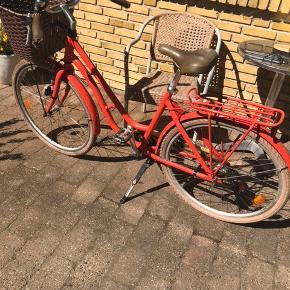 Flot orangerød Mustang cykel i 26 tommer. God robust cykelkurv. 7 gear.  Plastik dækslet foran kæderne er knækket så sat sammen med tape. Har ingen betydning andet end udseende. Kunne godt bruge nye dæk.