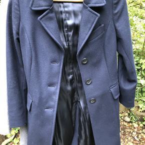 Mørkeblå frakke som sidder rigtig flot - den er i 80 procent uld. Jeg synes den er i pæn stand - men har skrevet god men brugt fordi den er brugt i nogle år og ikke er ny ligesom min grå og beige jakke.