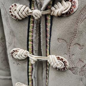 Retro ruskindsfrakke fra Munthe plus Simonsen med de smukkeste detaljer.  Super fin stand, dog er nogle enkelte syninger gået op i inderforet. Skriv endelig ved interesse.