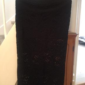 Blonde nederdel, den øverste del er med dobbelt stof og derfor ikke gennemsigtig, nederste del er et lag og man kan se gennem stoffet.