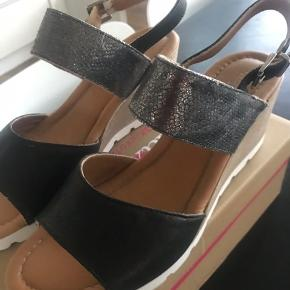 """Lækker sandaler med kilehæl fra """"relaxshoes """" i sort og sølv  Kun brugt 1 gang , da de desværre er for store ."""