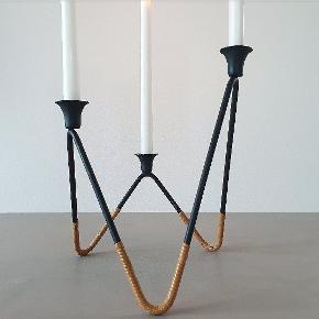 Grafisk stage i sort metal med bast fødder. Måler 21 cm hvor den er højest og passer til kertelys/juletræslys.