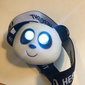 Pandelampe. Sjov og sej med pandahoved.  Øjnene lyser enten kontinuerligt eller blinkende. LED lys. Justerbar, elastisk bånd med kliklås. Alt virker.