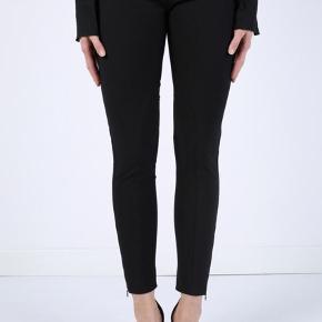 Fine sorte skinny bukser/leggings med strech. Er nogle år gamle , men den klassiske model fra Stella Maccartey laves sæson efter sæson og var også en del af FW 19/20 kollektionen. Buksernefremstår i flot stand og i den bedste ende af gmb, uden huller, pletter, fnuller eller lign. En italiensk 36, der konverterer til en dansk str 32/xs. 58% cotton, 35%/ polyamid ogn7% elasten. Bukserne har elastik i taljen med lynlås bagpå. Der er desuden en skjult lynlås nederst i benende.  Taljemål: 30 cm på tværs når elastikken ikke er udstrakt, dvs 60 cm i omkreds når elastikken ikke er udstrakt. Udvendig benlængde: 95 cm fra livet og ned. NB det hvidlige på et af mine billeder er blitz... Søgeord: sorte skinny bukser pants leggings cotton bomuld stramme sort Black