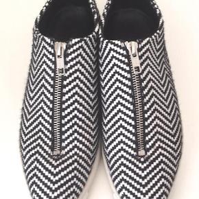 Smuk Stella McCartney sneaker i sort/hvid stribet textil med front lynlås.Brugt få gange, eneste tegn på brug er på sålerne.Kommer med skopose, ingen box. Betaling via MobilePay foretrækkes.  Sneakers Farve: Sort/hvid Oprindelig købspris: 4350 kr.