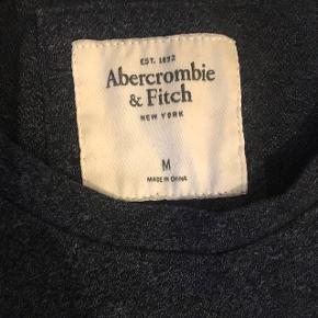 Grå/blå t-shirt fra abercrombie & fitch.  Kun brugt et par gange, der er dog et par løse snore på logoet i midten.  Bytter ikke.  Køber betaler selv fragt.