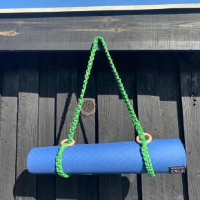 Håndknyttet macrame bærestrop til yogamåtte.  Stroppen er unik idet den er håndlavet af genbrugstræringe og recycled cotton yarn, som er et overskudsprodukt fra tekstilindustrien. Stroppen er en smule elastisk.  Farve: grøn ➰ ➰ Str M. (Ca 140 cm uden træringene) Pris pp 150 kr.