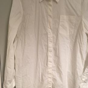 Skjorte i stretch stof, bomuld og elastan. Lidt oversize i modellen. Fin stand. Kun brugt 1 gang. Lidt længere bag på. Skjult knappelukning. Den er lidt krøllet, men ellers er den i god stand.   50,- + fragt. Sender gerne med Dao.  Bytter ikke.
