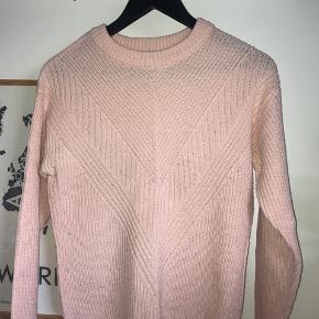 Svagt lyserød/laksefarvet sweater.