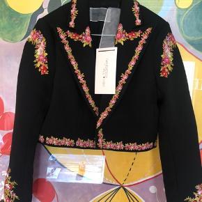 GIAMBATTISTA VALLI x H&M - Designsamarbejde i Nov 2019. Blev udsolgt med det samme! Kort jakke i kraftig, vævet kvalitet med detaljerede broderier. Jakken har krave og spids revers. Ny pris 1299kr.