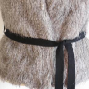 """100% NY: Super smart vest i grålig """"pels"""" med sort bindebælte. Vesten er med foer.  Størrelse: str. S/M  Brystvidden: 48 cm x 2, men er flexibel, da man kan binde vesten mere eller mindre tæt. Hoftevidde: 50 cm x 2 Længde: 57 cm  Ingen byt, og prisen er fast"""